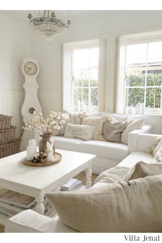 Cozy warm white Swedish living room with all white decor and Mora clock - Villa Jenal. #whitelivingroom #whitedecor #scandistyle
