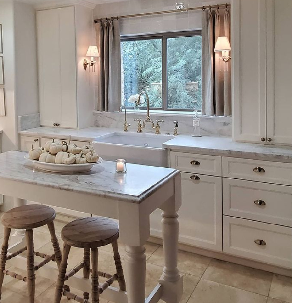 Serene elegant sophisticated white French kitchen with petite island and sconces flanking farm sink - The French Nest Co Interior Design. #whitekitchens #modernfrench