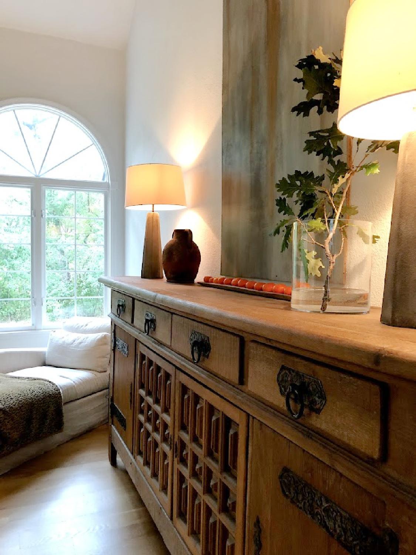 Rustic antique Belgian sideboard with oak branch in vase in early fall - Hello Lovely Studio.