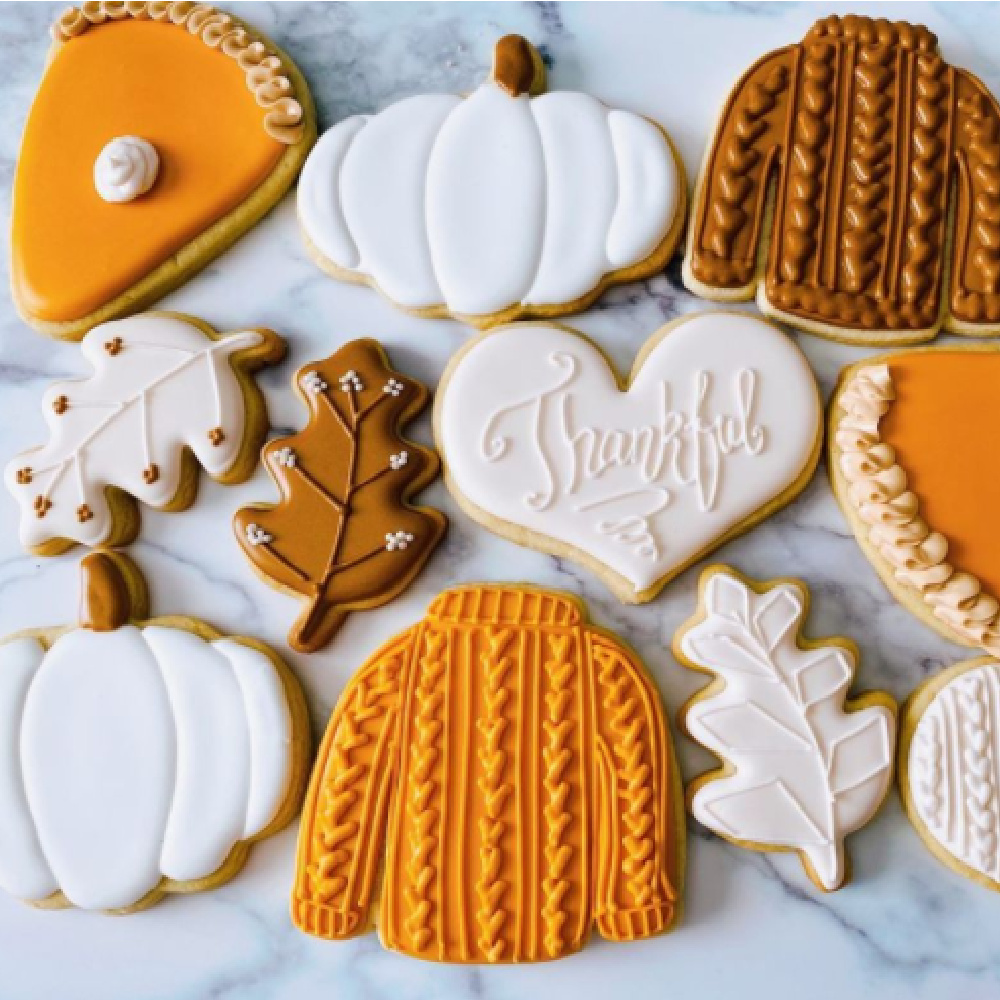Charmingly sweet Thanksgiving fall autumn frosted cookies in pumpkin, sweater, and leaf shapes - @cookiebosshtx. #fallcookies