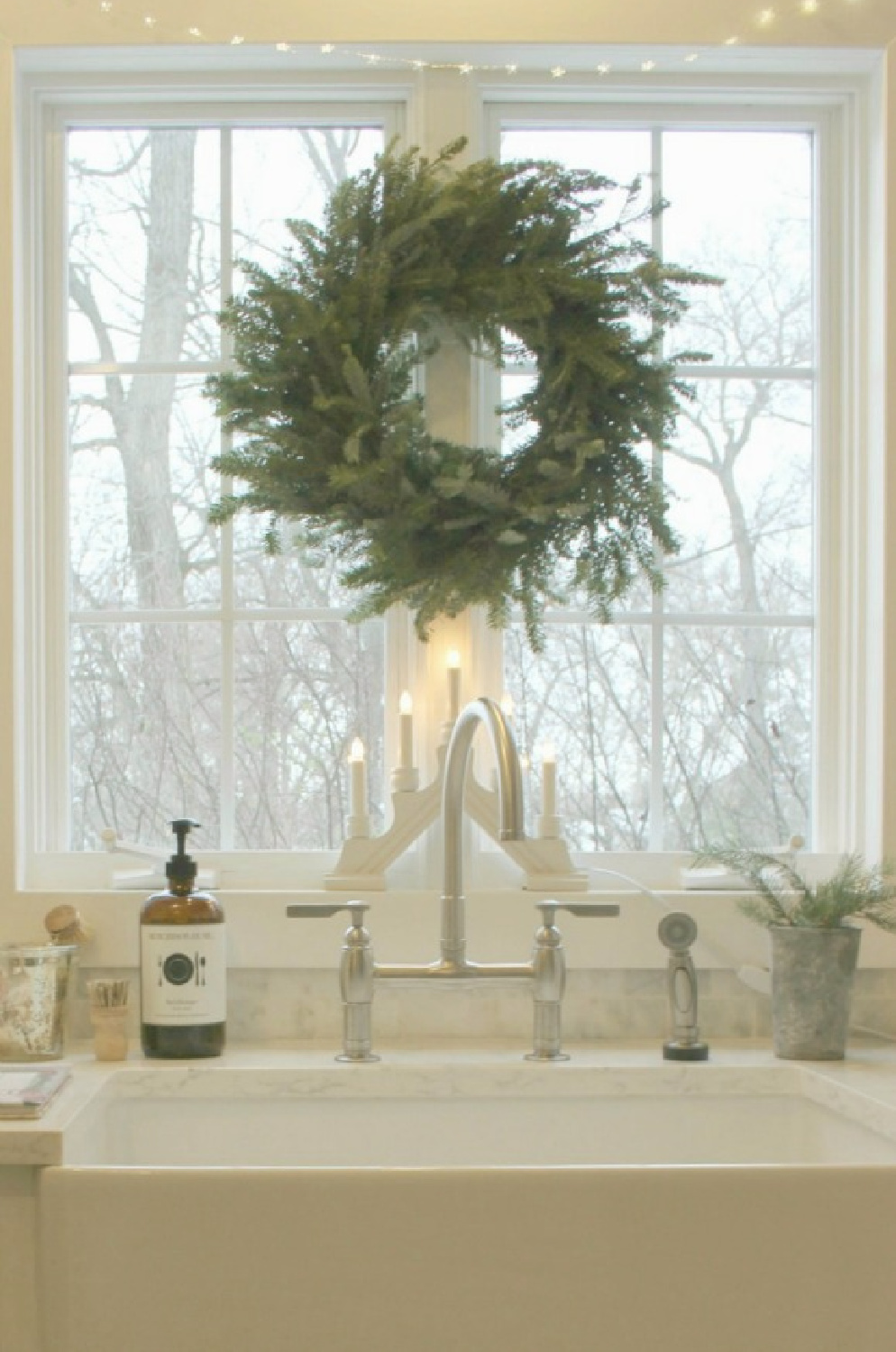 My Christmas kitchen with Scandinavian style and a fresh wreath over farm sink - Hello Lovely Studio. #swedishchristmas