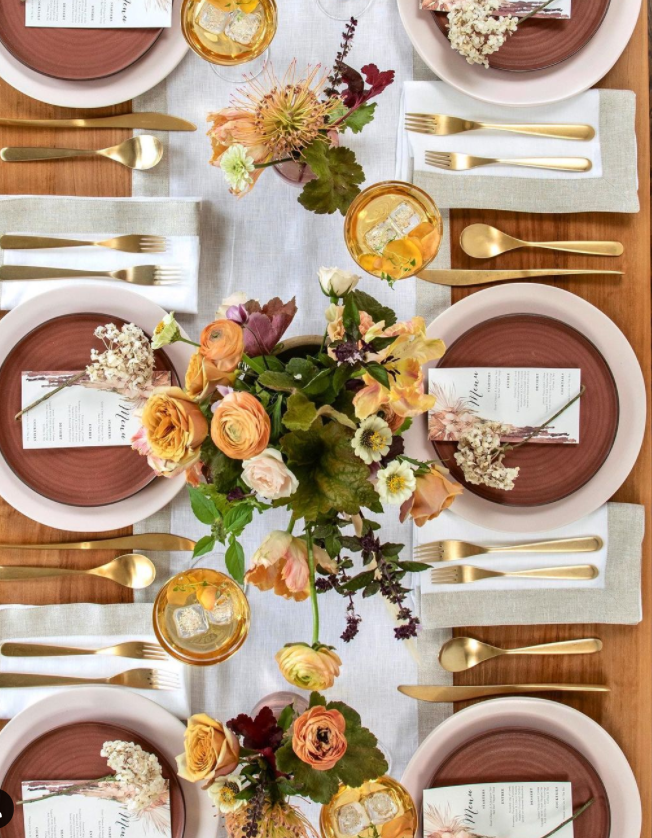 Neutral Thanksgiving or fall tablescape with rust accents, linen, and fresh florals - @tableanddine. #falltablescape #thanksgivingtable #centerpieces