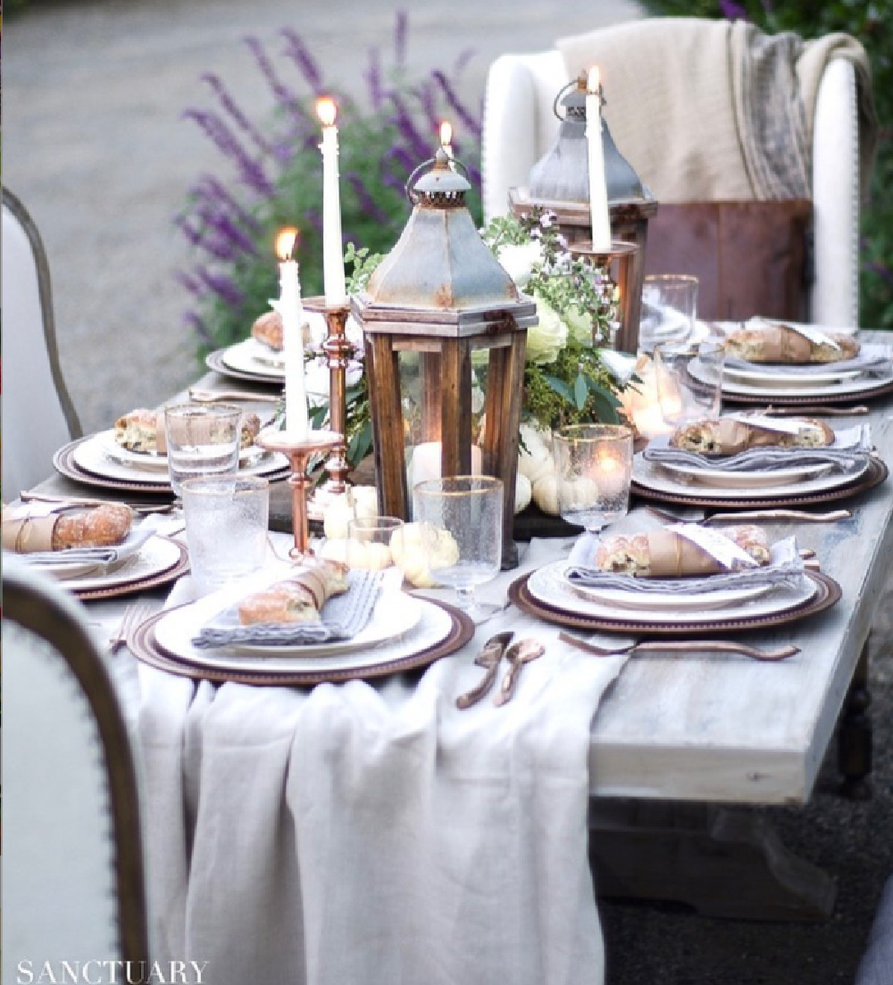 Outdoor Thanksgiving tablescape with French farmhouse style, rustic lanterns, and elegant chairs - @sanctuaryhomedecor. #thanksgivingtable #tablescapes #frenchfarmhouse