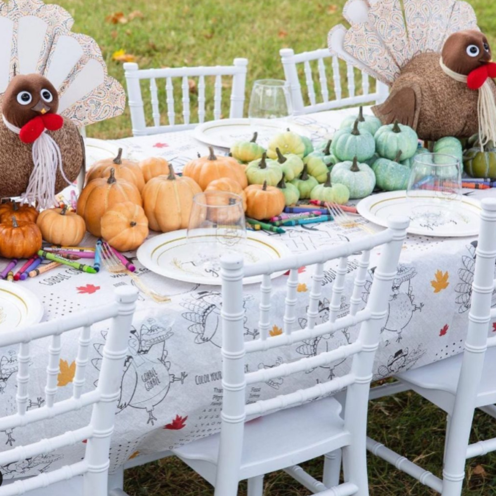 Whimsical Thanksgiving kids table tablescape with turkeys, pastel pumpkins, and outdoor setting - @mrssouthernsocial. #thanksgivingtable #tablescapes #kidstable