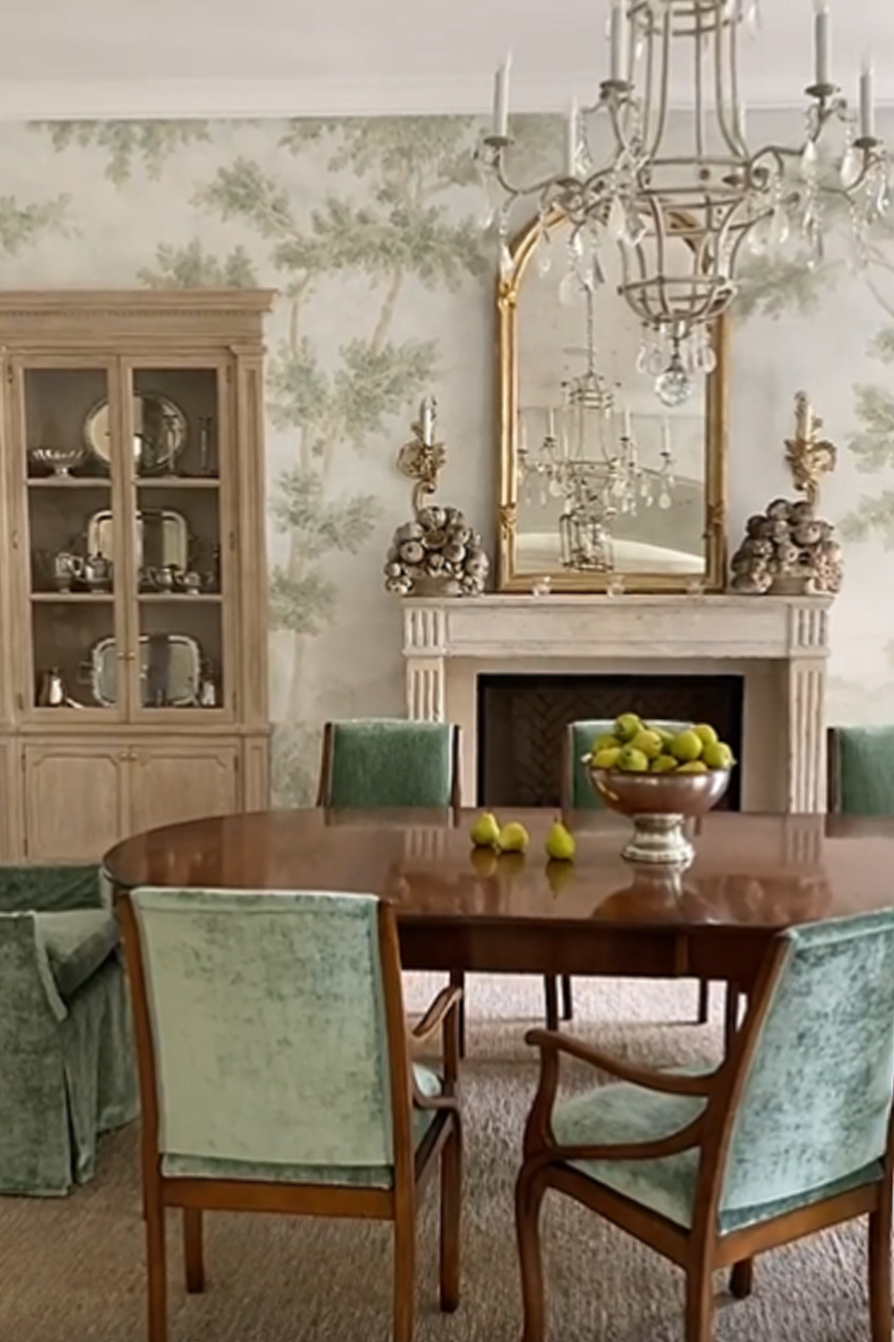 Elegant French country dining room with green accents, tree mural, and antique fireplace from Exquisite Surfaces - design by Giannetti Home. #interiordesign #diningrooms #traditionalstyle