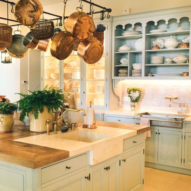 French farmhouse kitchen in Provence with light blue cabinets and copper pots from E. Dehllerin - @provencepoirers. #frenchkitchen #frenchfarmhouse #frenchchateau #copperpots #frenchfarmhousekitchen #lightblue #provencekitchen #provencepoirers