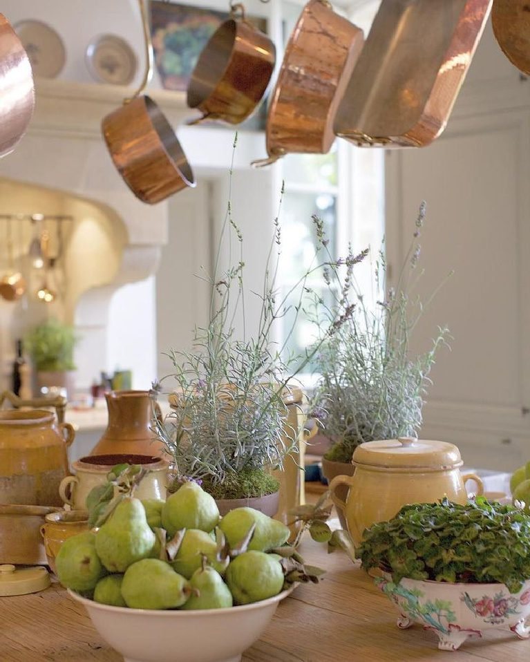 Lovely green pears and French countryside bounty on a French country kitchen island beneath copper pots from E. Dehllerin - @provencepoierers. #frenchcountry #copperpots #frenchkitchen #provencekitchen #pears #frenchpears #provencepoirers