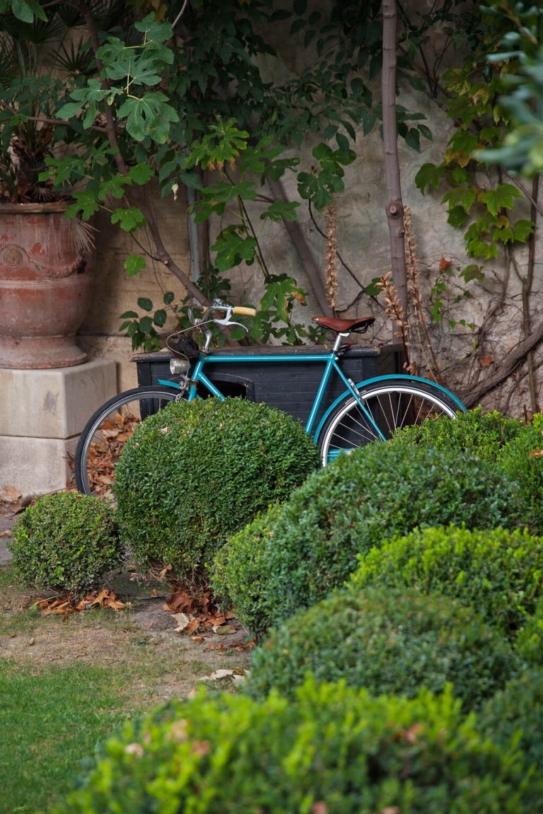 Charming boxwood gardens and bicycle at Avignon Hôtel Particulier, a beautifully restored 19th century Provence manse in the heart of Avignon's historic center - Haven In. #frenchcountrygarden #frenchchateau #provence #frenchcountry #restoredchateau #southoffrance #aivgnonhotel