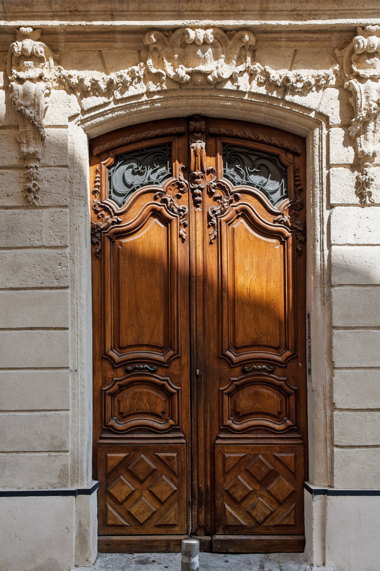 Architecturally magnificent carved wood doors and stone facade of a building near Avignon Hôtel Particulier, a beautifully restored 19th century mansion in the heart of Avignon's historic center - Haven In. #frencharchitecture #oldworldstyle #carveddoors #frenchchateau #provence #frenchcountry #southoffrance