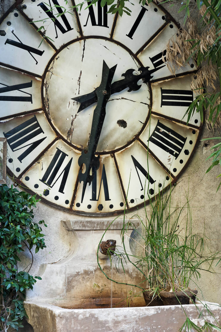 Antique stone fountain below  large roman numeral clock on a stone building - Avignon Hôtel Particulier, a beautifully restored 19th century mansion in the heart of Avignon's historic center - Haven In. #antiquefountain #stonefountains #frenchcountrydecor #frenchchateau #provence #frenchcountry #restoredchateau #southoffrance #aivgnonhotel
