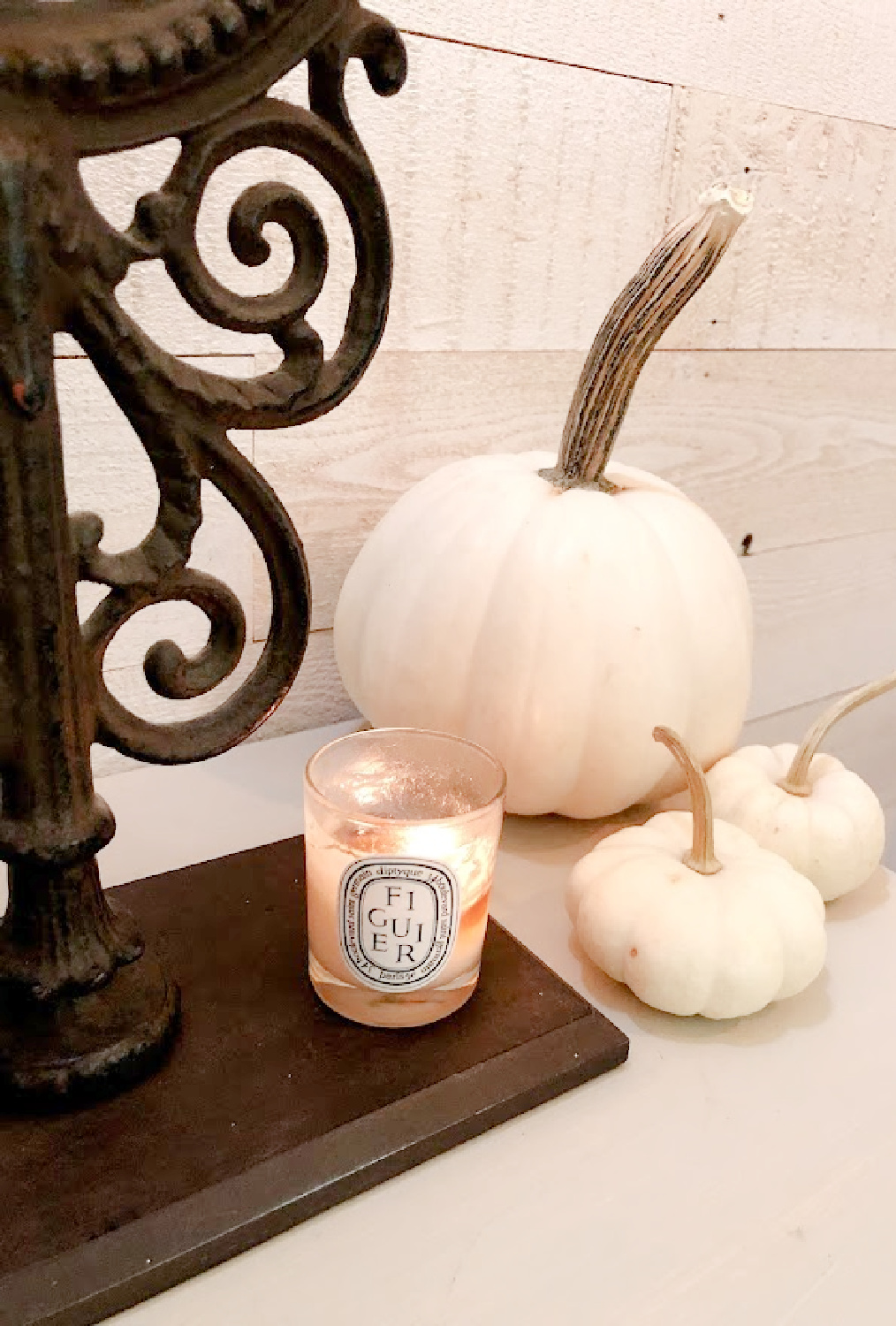 White pumpkins and Diptyque Figuier candle in my fall bedroom - Hello Lovely.