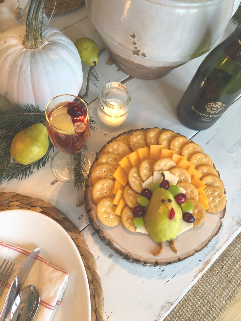 Silly pear turkey on a cheese board for Thanksgiving - Hello Lovely Studio. #thanksgivingrecipes #thanksgivingtable