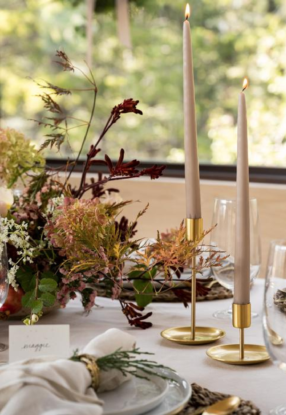 Brass candle holders and sandstone candles on a lovely neutral and natural holiday table by McGee & Co.