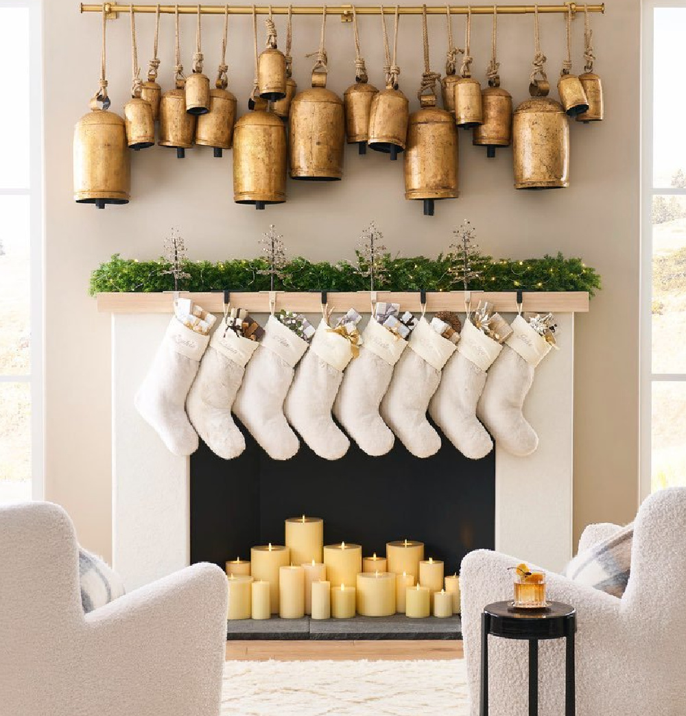 Gold Christmas bells suspended from track over a fireplace with greenery and candles - Pottery Barn. #christmasbells #goldbells #christmasdecor