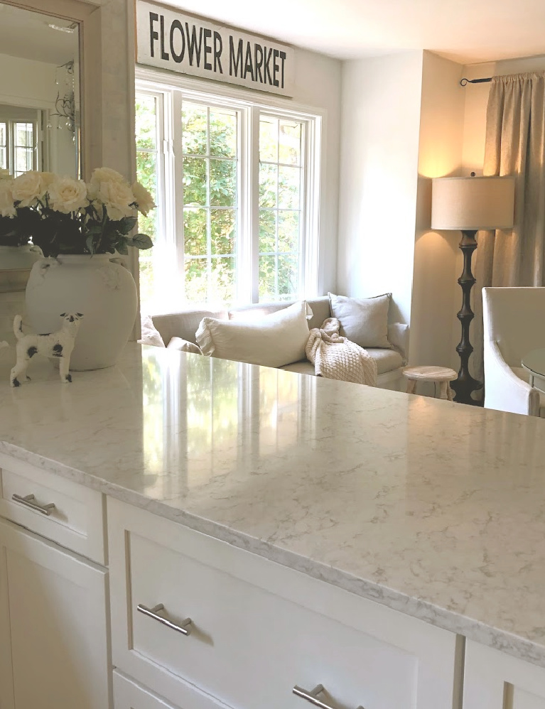 Serene white kitchen with LG Viatera Minuet quartz counters, Shaker cabinets, window seat, and white roses in French pot - Hello Lovely Studio. #hellolovelystudio #kitchendesign #lgviatera #minuet #whitequartz #windowseat #frenchcountry #europeancountry