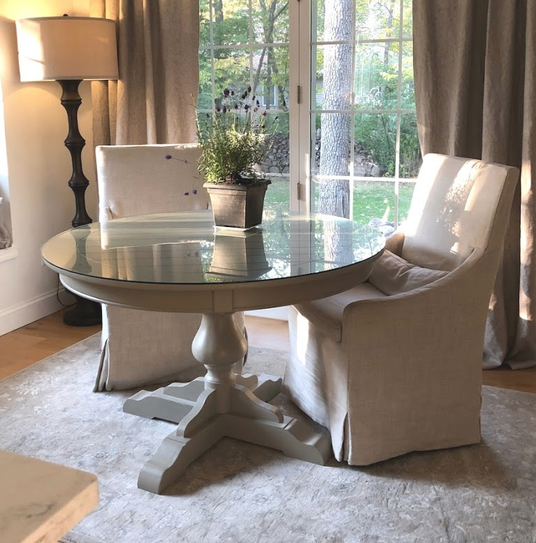 Serene Decor in our breakfast nook with Belgian linen slipcovered chairs, round dining table, and Couristan area rug - Hello Lovely Studio. #hellolovelystudio #breakfastnook #belgianlinen #slipcoveredchairs #cozykitchen #europeancountry #frenchcountrystyle