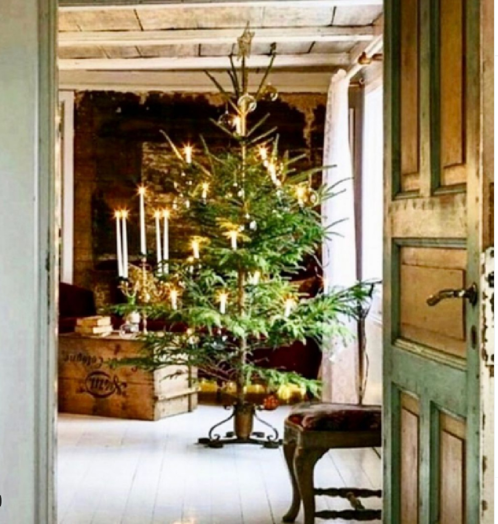 Swedish Christmas tree and candles in an old home with vintage weathered door - Portobello Design. #swedishchristmas #scandichristmas #holidaydecor