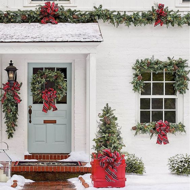 Charming white brick exterior of a country home decorated for Christmas with greenery and plaid ribbon - Frontgate. And that light blue door!