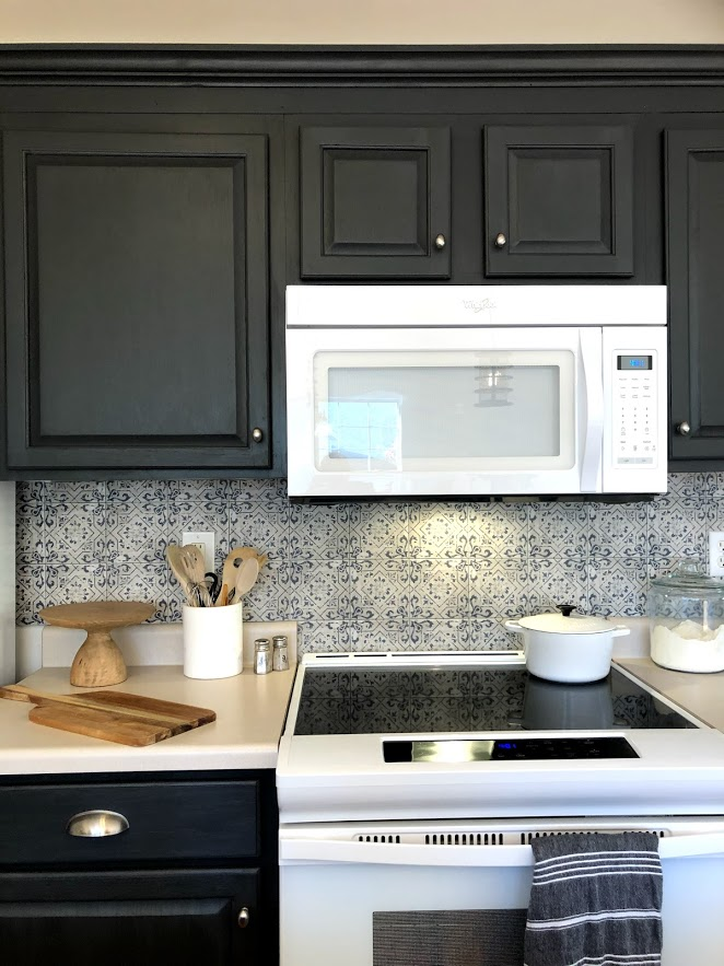 A modern white Whirlpool electric range contrasts with dark gray cabinets and a Spanish tile backsplash.