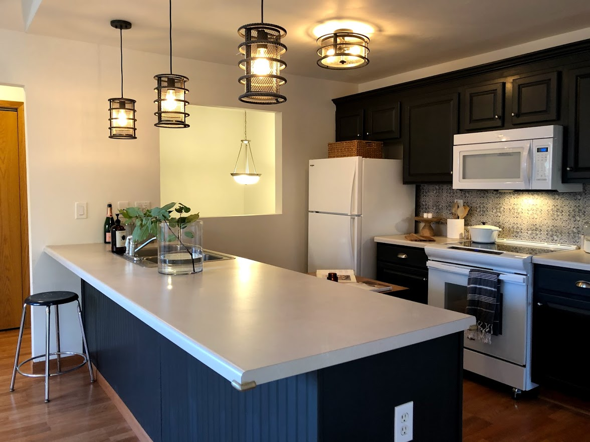 Crisp white walls contrast with the deep dark blue/gray cabinets (Sherwin Williams Carbonized).