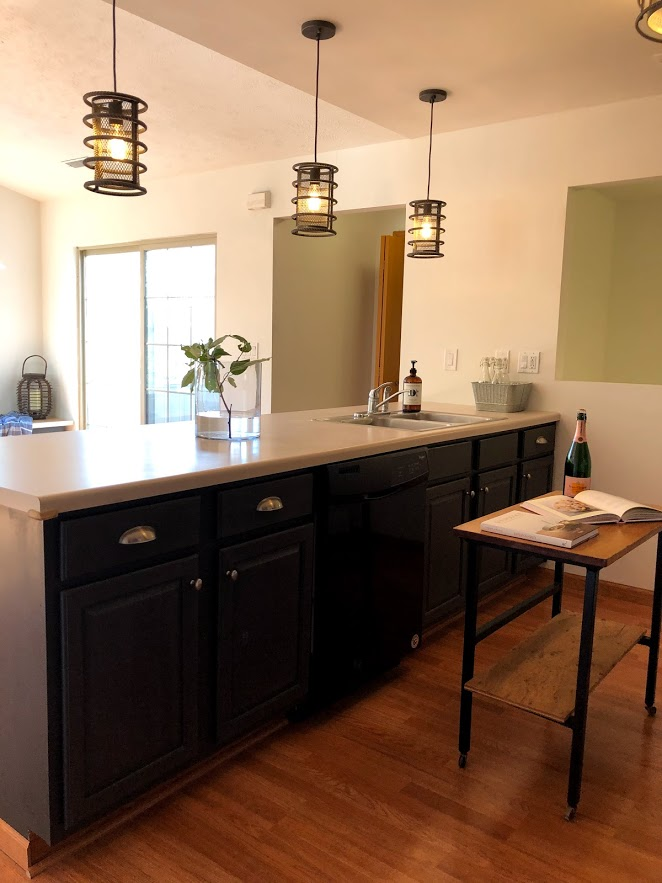 Three industrial style pendant lights over a breakfast bar with cabinets painted Sherwin Williams Carbonized - a deep dark charcoal.