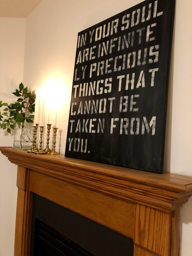 Oak fireplace surround with brass candlesticks, a simple branch, and artwork from Hello Lovely Studio with quote from Oscar Wilde.
