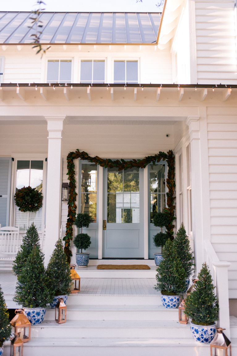 Charming, traditional and classic white and blue porch decorated for Christmas with magnolia garland, mini trees in porcelain planters and topiaries - Julia Berolzheimer.
