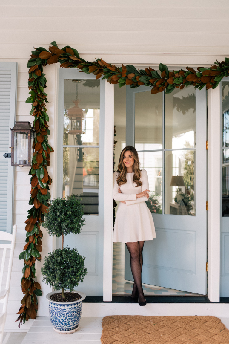 Charming, traditional and classic white and blue porch decorated for Christmas with magnolia garland and topiary - Julia Berolzheimer.