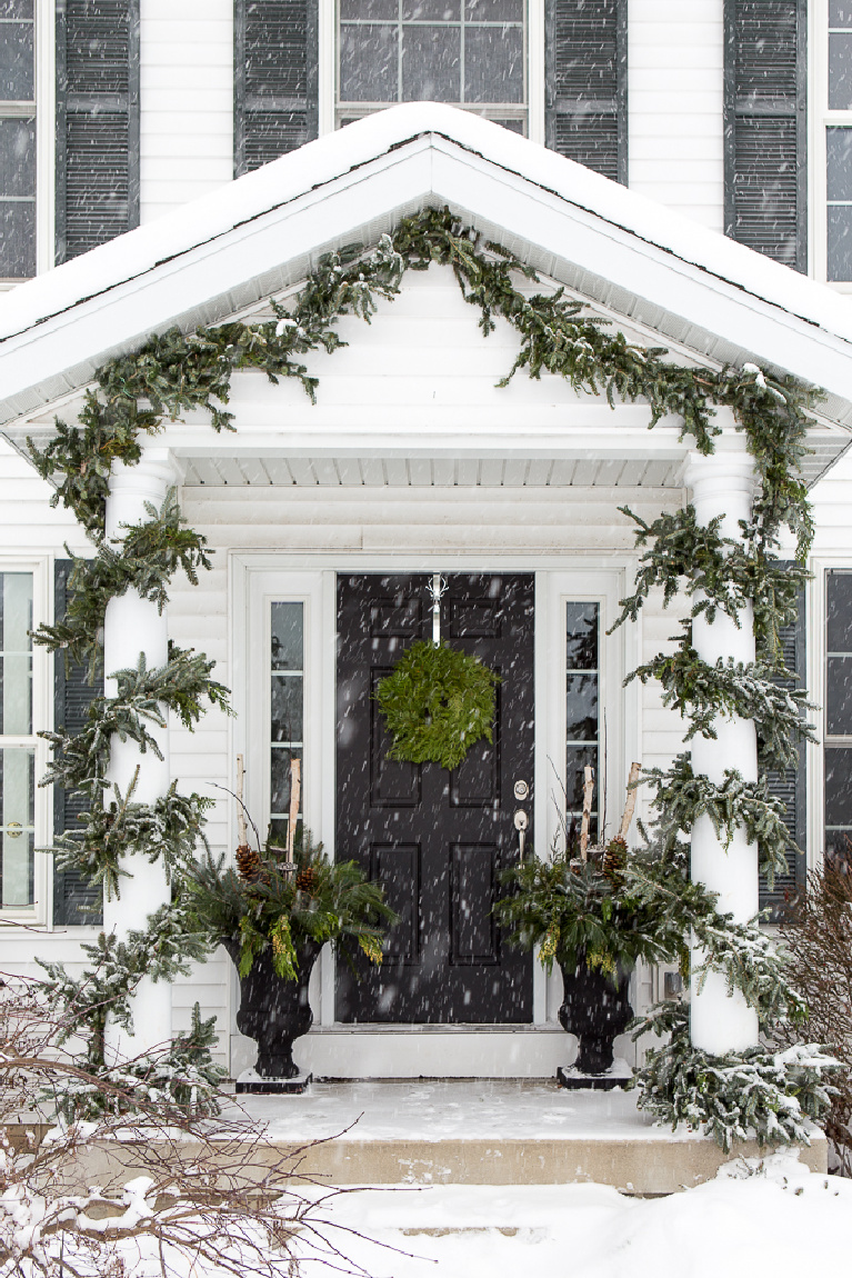 Beautiful white traditional house exterior with black door decorated for Christmas with garland and wreath - Just a Girl Blog.