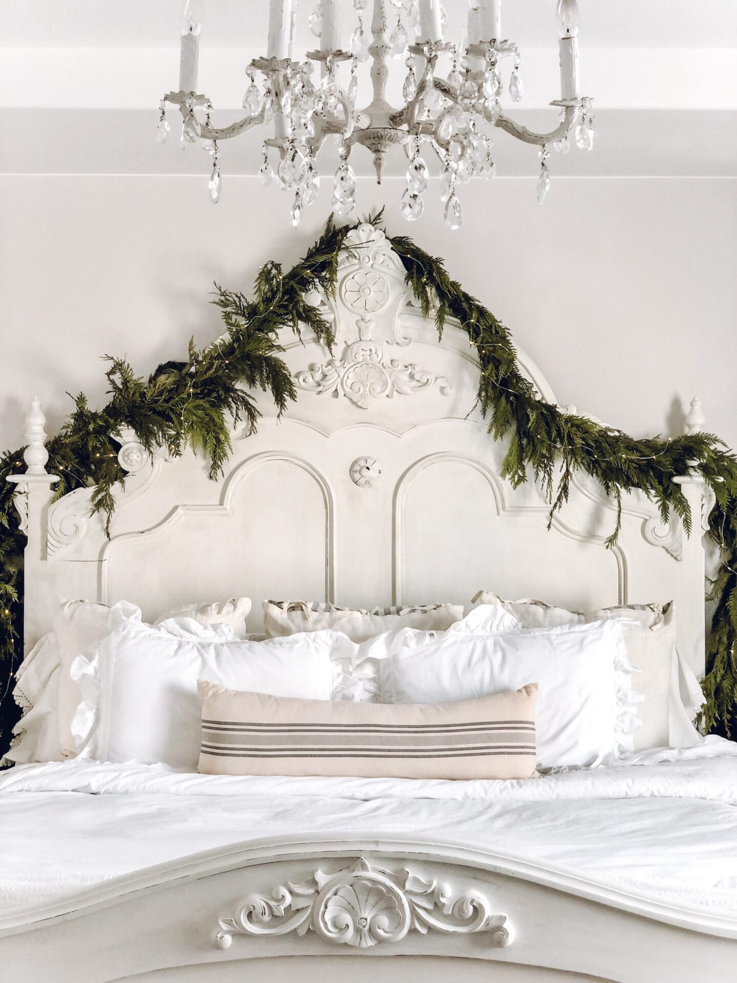 Charming country cottage white bedroom with antique headboard decorated simply with fresh greenery - Le Cultivateur. #holidaydecor #christmasgarland #bedrooms