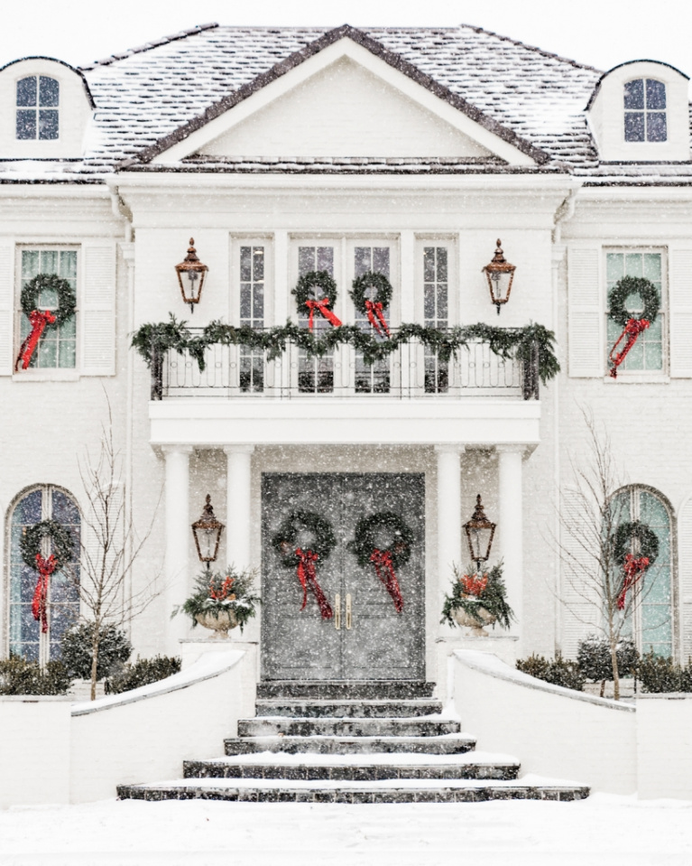 Breathtaking and traditional white grand home with fresh green Christmas wreaths in every window! Rach Parcell.