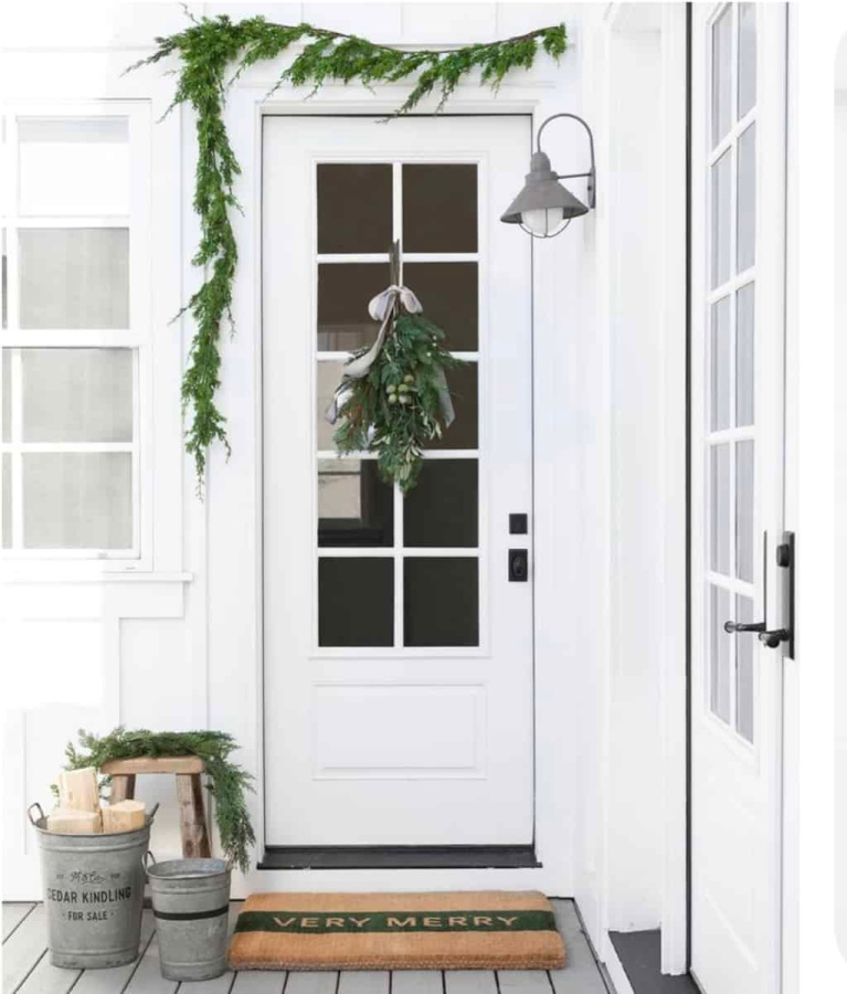 White farmhouse exterior decorated for Christmas simply with fresh greenery, doormat, and galvanized buckets - Studio McGee.