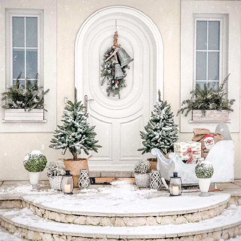 Enchanting home exterior with white arched door and Christmas decorations including bells, greenery in window boxes, and Santa's sleigh - @Basniowy.