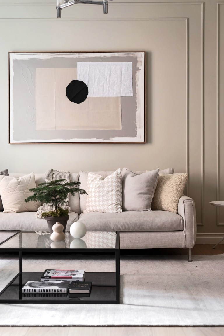 Cozy neutral beige living room in a Swedish home with modern art and calm design style - PlaneteDeco.