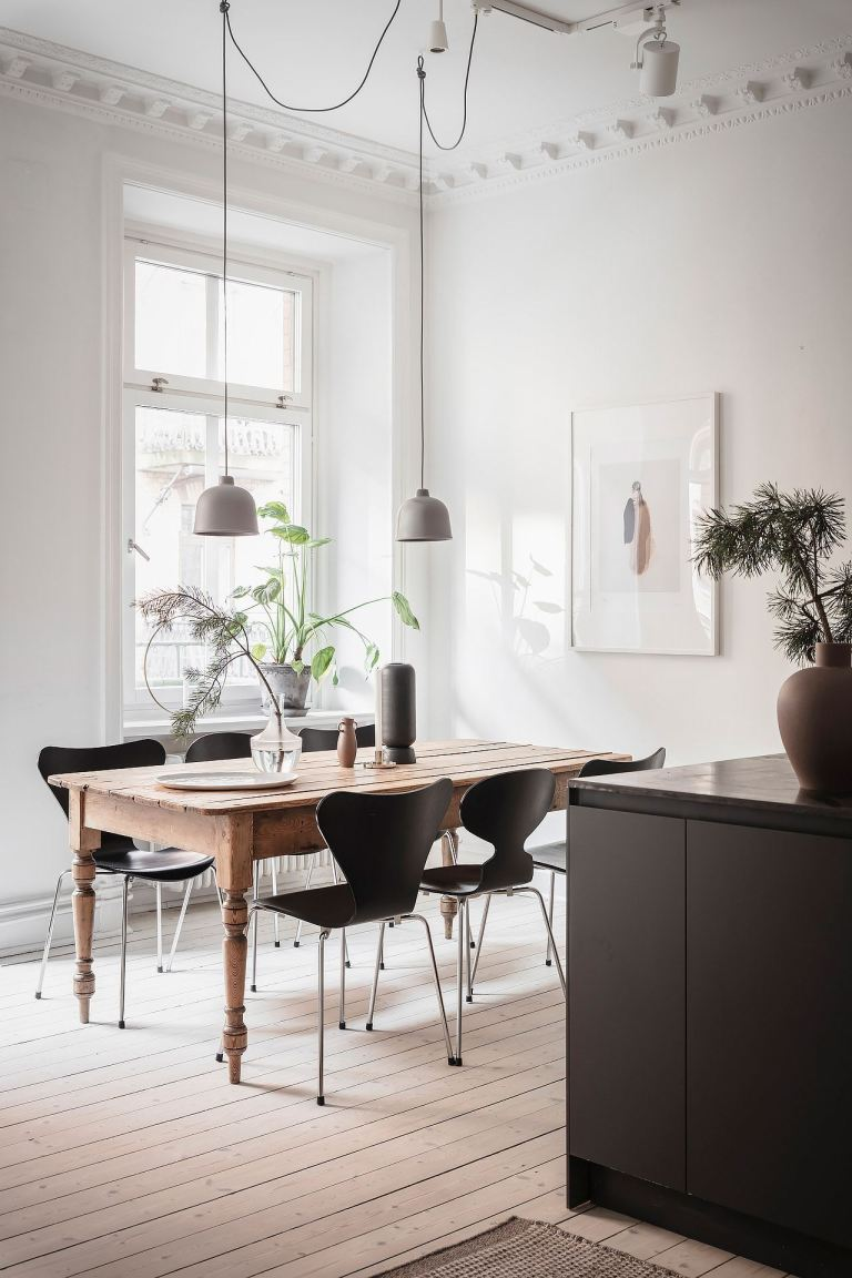 Zen dining room with white walls, modern black chairs, and natural wood farm table exuding Scandinavian style - PlaneteDeco.