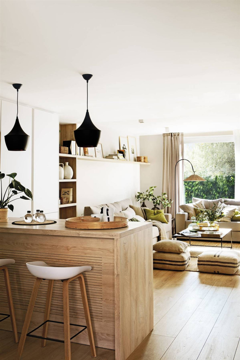 An open kitchen in Barcelona with calm, zen, natural modern style and black pendants over breakfast bar - Pia Capdevilla.