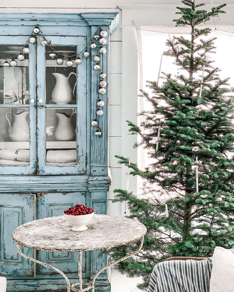 Serene beautiful French farmhouse Christmas decor with old blue cupboard full of ironstone and Christmas tree - DreamyWhites. Enjoy Glorious 2020 Holiday Decorations & Inspiring Quotes for 2021 Now!