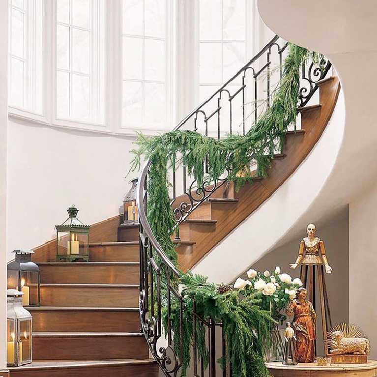 Elegant Christmas garland on a beautiful staircase with wrought iron railing - Cindy Hattersley.
