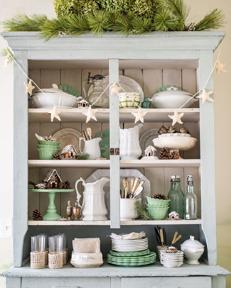 Christmas decor in a charming light blue country cupboard with open shelves and vintage dishware including jadeite - Miss Mustard Seed.