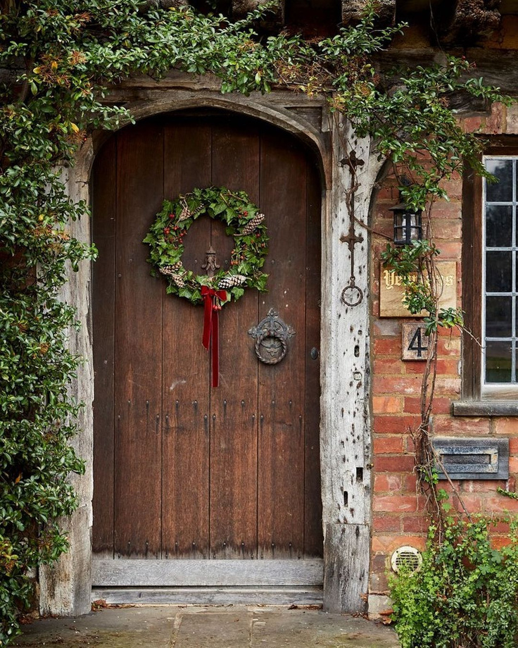 Beautiful cottage with arched wood door hung with Christmas wreath - @hunt_the_pearl. Enjoy Glorious 2020 Holiday Decorations & Inspiring Quotes for 2021 Now!