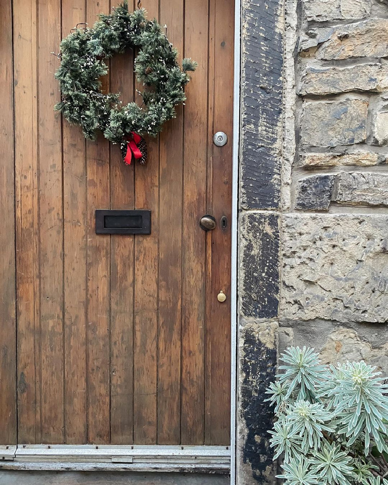 Charming Christmas wreath on an old planked wood door of a stone cottage - @home_stead