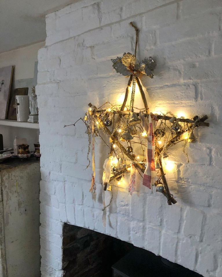 Charming and rustic Christmas star made from twigs against a white brick hearth - MySimpleHome. Enjoy Glorious 2020 Holiday Decorations & Inspiring Quotes for 2021 Now!