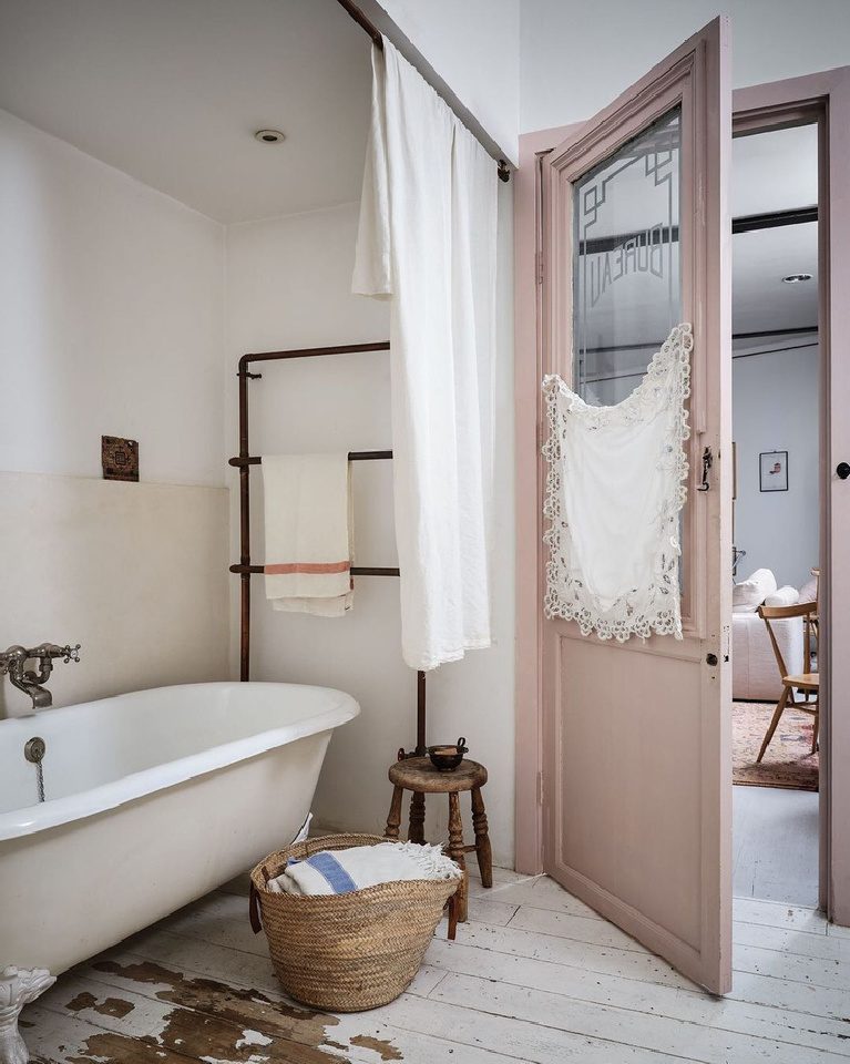 Serene rustic vintage zen bathroom with clawfoot tub, pink door, and white floors - design by Clare Lattin and appearing in HOME FOR THE SOUL by Sara Bird & Dan Duchars (Ryland Peters Small, 2020).