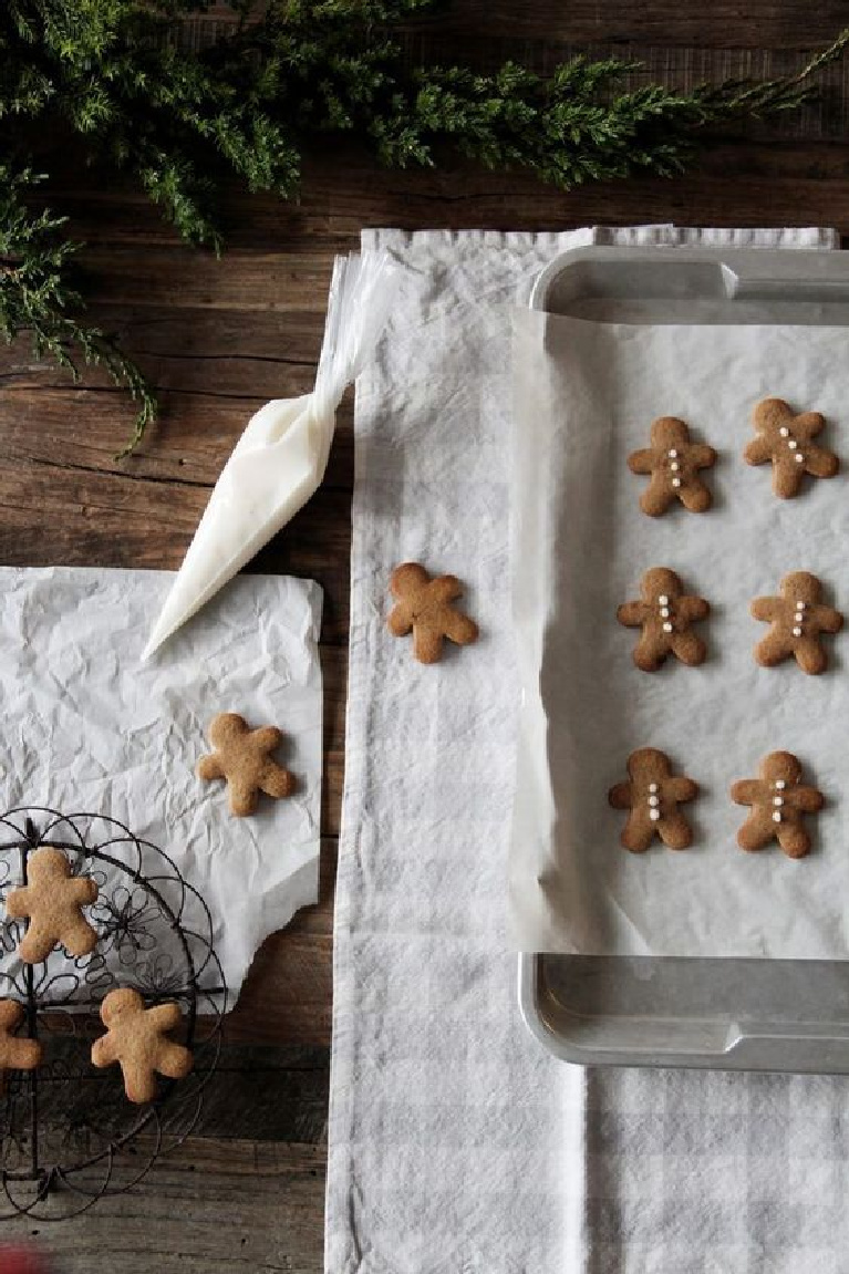 Charming flatlay image of mini gingerbread men cookies on a rustic farm table being iced simply - Scandinavian style Christmas decor beauty - ForkandFlower.
