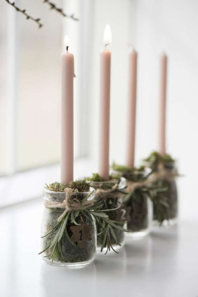 Simple Scandinavian Christmas decor idea with little glass jars of moss to hold candles and sprigs of rosemary tied with twine at top. #scandinavianchristmas #tablescape #candleholders