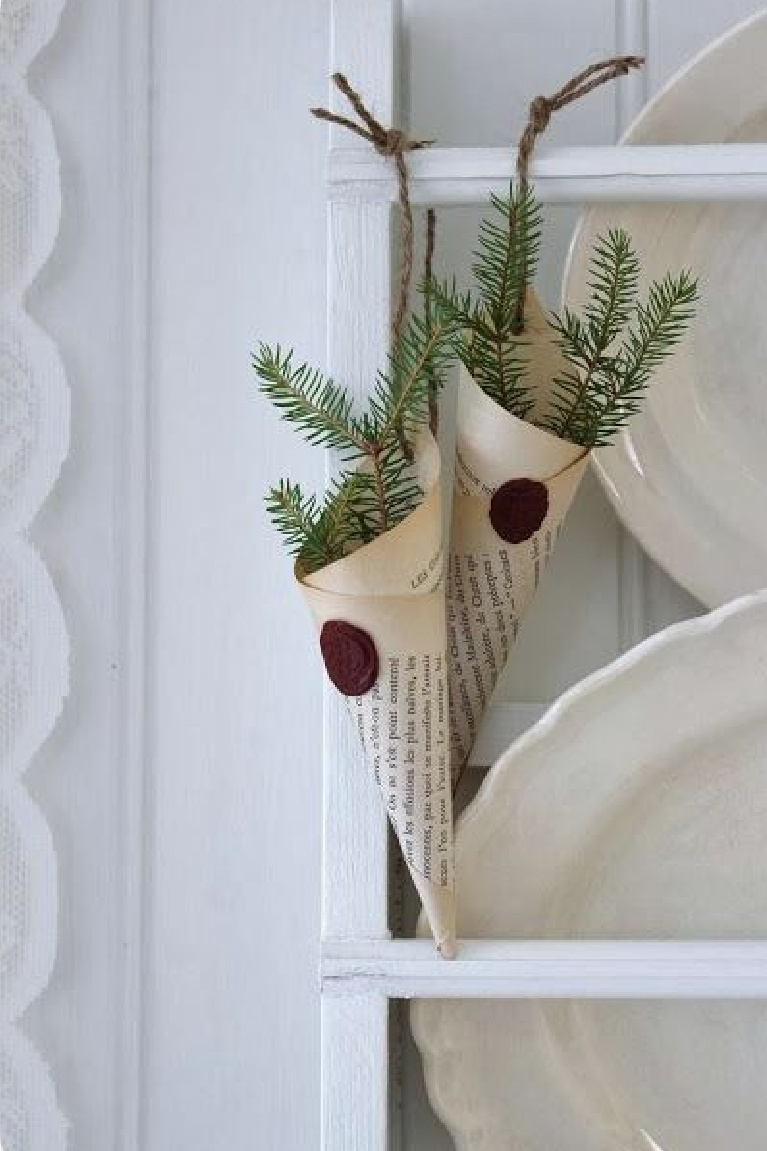 Charming book page cones with wax seal and greenery for Scandi simple Christmas decor on a platerack with white vintage ironstone - Lillablanka.