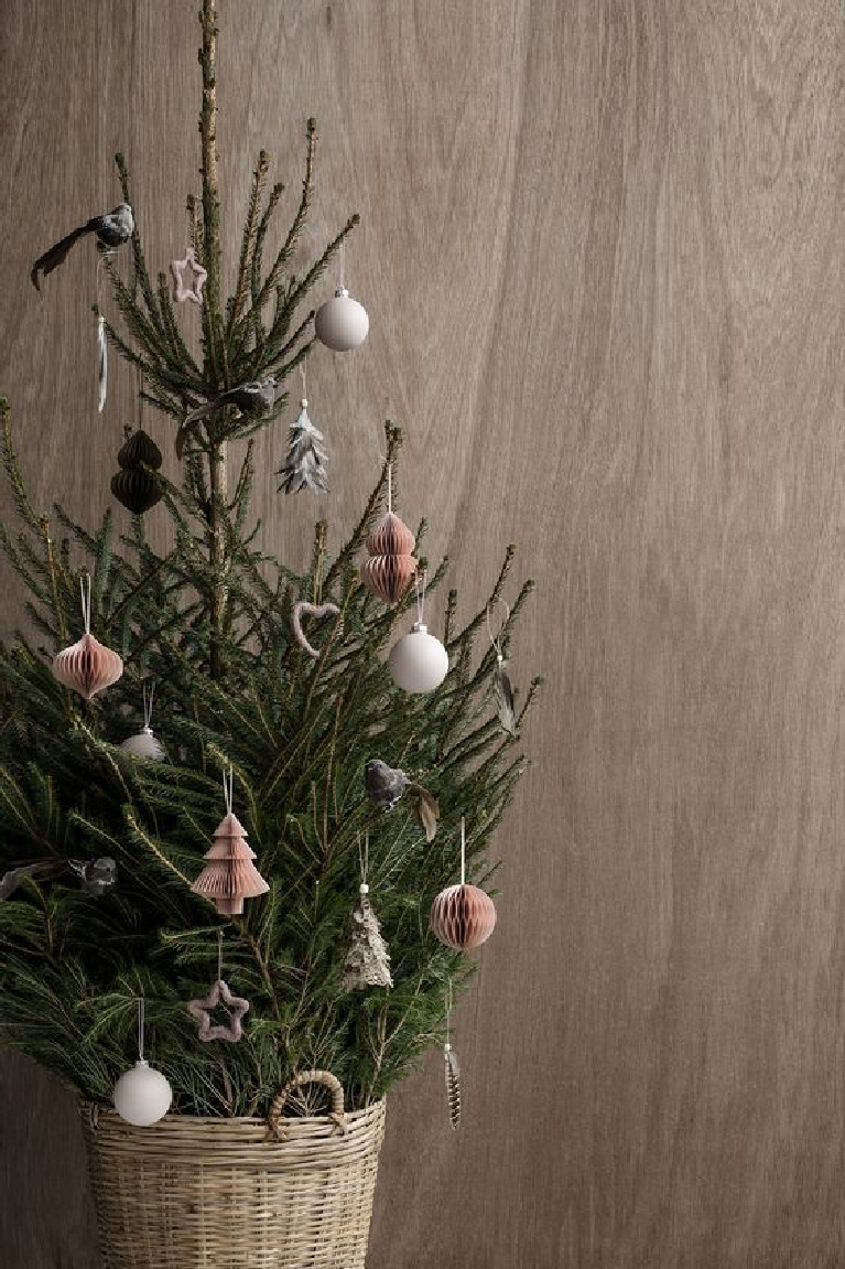 Scandinavian Christmas decor - a small fresh Christmas tree in handled basket with paper ornaments looks modern and serene against a wood backdrop - Bloglovin.