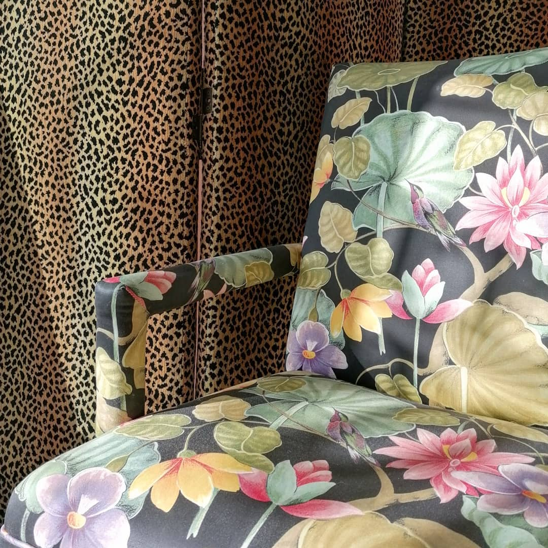 1980s colorful print upholstered arm chair with floral and hummingbirds against an animal print drape - @sideshowinteriors.