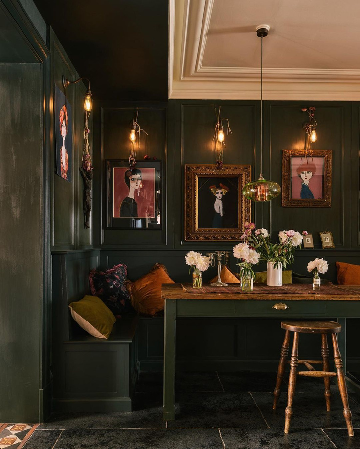 Moody dark green painted paneled walls and furniture in a kitchen dining area with industrial sconces and bespoke design - deVOL.