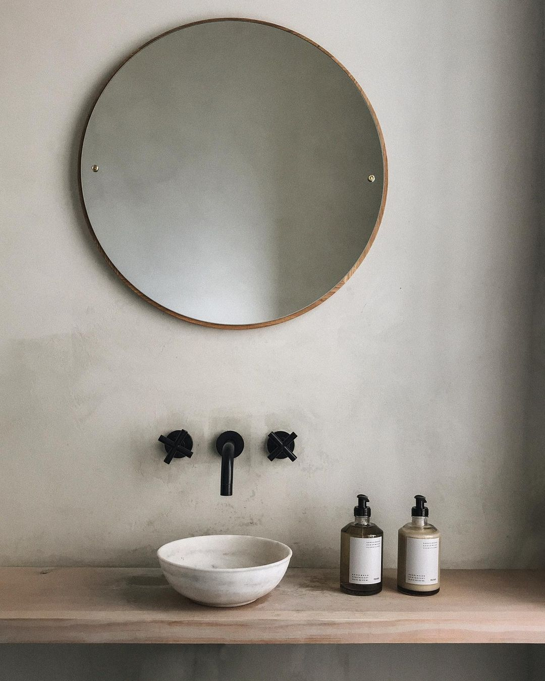 Serene, minimal, rustic bathroom design with vessel sink and round mirror - @framacph.